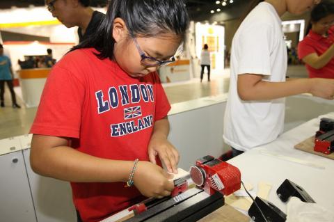한 여학생이 미니 공작기계 '유니맷(UNIMAT)'시리즈를 가지고 무엇인가를 제작하고 있다.  이 공작기계는 인체에 손상을 주지않으면서 톱, 표면을 갈아주는 샌딩(sanding), 선반, 핸드드릴, 금속 선반, 수직 밀링 등의 기능이 모두 가능하다.