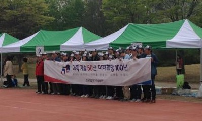 연구개발특구진흥재단 소속 참가자들이 '과학기술 50년, 미래희망 100년' 표어가 적힌 플래카드를 들고 기념촬영을 하고 있다.