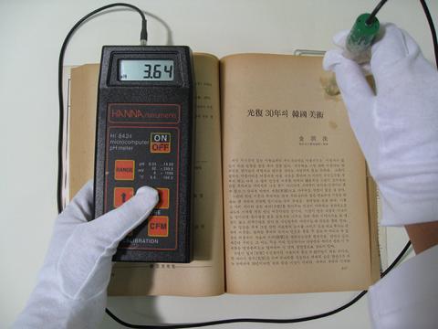 산성화된 종이 책의 산성도를 측정하고 있는 모습. ⓒ 국립중앙도서관 제공