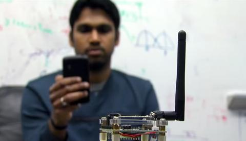 연구원이 '패시브 와이파이' 장치(앞부분)를 이용해서 스마트폰으로 자료를 검색하고 있다.