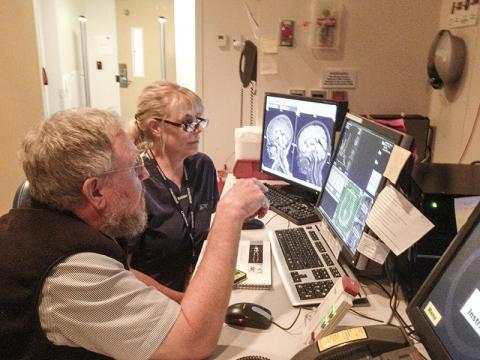 MRI기술자인 민디 딕슨과 스티븐 대거 교수(왼쪽)가 어린이의 뇌 화학 자기공명 분광 이미지를 검토하고 있다.  Credit: University of Washington