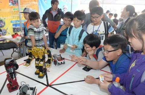 지난해 국립부산과학관에서 열린 '제15회 부산과학축전'에 참가한 어린이들이 부산시어린이회관 부스에서 휴머노이드 로봇과 보행 로봇을 조종해보고 있다.