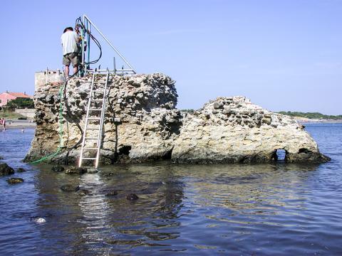 2003년 ROMACONS 프로젝트의 일환으로 연구재료를 확보하기 위해 이탈리아 토스카나 주 포르투스 코사누스의 해양구조물에서 구멍을 뚫고 있는 모습.  Credit: J. P. Oleson