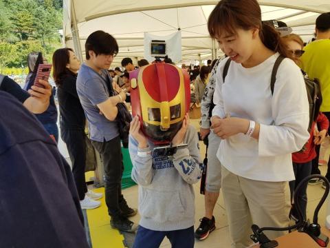 조현서 학생이 만든 아이언맨 마스크를 써보고 있는 관람객 어린이 ⓒ 김순강 / ScienceTimes
