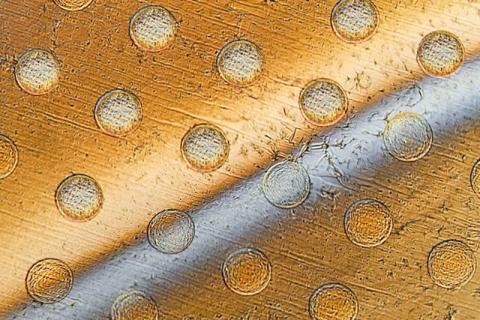 둥근 기둥 배열 위에 걸쳐진 그래핀 시트에 둥근 구멍들이 생긴 모습. 시트를 가로지르는 회색 막대는 표면에서 디스크를 들어올리는 액체. Credit: Felice Frankel