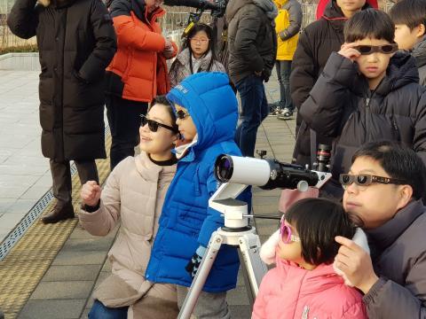 셀로판테이프를 붙인 일명 '태양일식관측기'를 통해 부분일식을 보고 있는 가족들 ⓒ 김순강/ScienceTimes