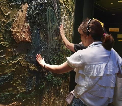 유정 아트센터를 찾은 관람객이 빈센트 반 고흐 뮤지엄 에디션 '추수'를 손으로 직접 만져보고 있다.ⓒ김민아
