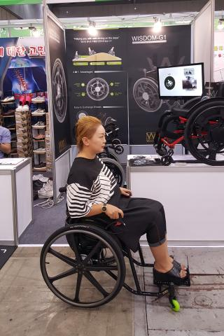 문현덕씨가 자신의 발명품인 휠체어 안전 브레이크시스템이 장착된 휠체어에 앉아 작동해 보이고 있다.