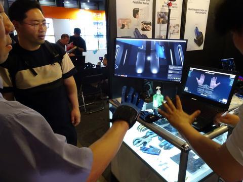 한 참관객이 울산과학기술원(유니스트, UNIST) 배준범 교수팀이 개발한 VR 장갑을 체험하며 놀라고 있다. ⓒ 김은영/ ScienceTimes