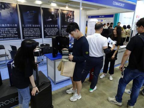 가방 주인 뒤를 졸졸 따라다니는 'AI 자율주행 캐리어'를 참관객들이 신기하게 보고 있다.     ⓒ 김은영/ ScienceTimes