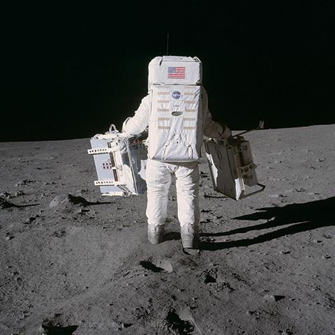 왼손으로 지진계(PSEP), 오른손으로 레이저 반사장치(LR3)를 들고 이동 중인 버즈 올드린 © NASA