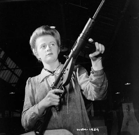스텐 기관단총을 들어보이는 여성 노동자. 근본적으로 위력이 약한 권총탄을 쏘는 기관단총이기 때문에 그만큼 만드는 데 시간과 돈이 적게 들었고, 여성이나 청소년, 노인들도 쏘기 쉬웠다.  ⒸWikipedia