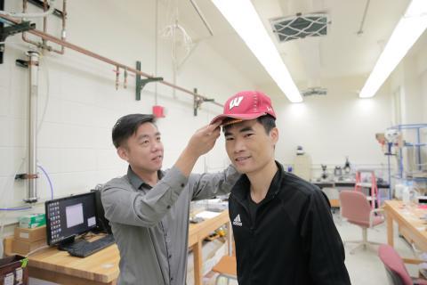 왕 교수(왼쪽)가 '나노 발전기' 모자를 씌우고 있다.
